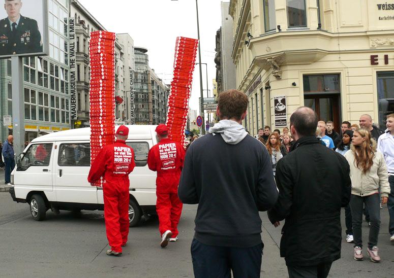 Männer tragen hohen Stapel Papier