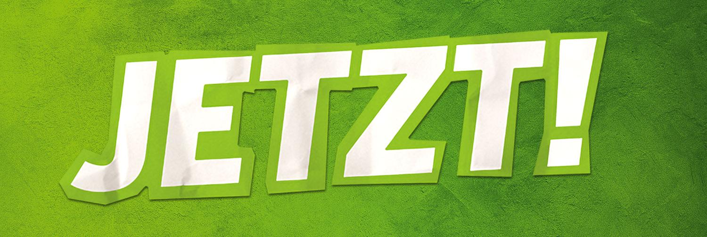 Headerbild - Das Wort Jetzt aus Papier ausgeschnitten auf grüner Wand