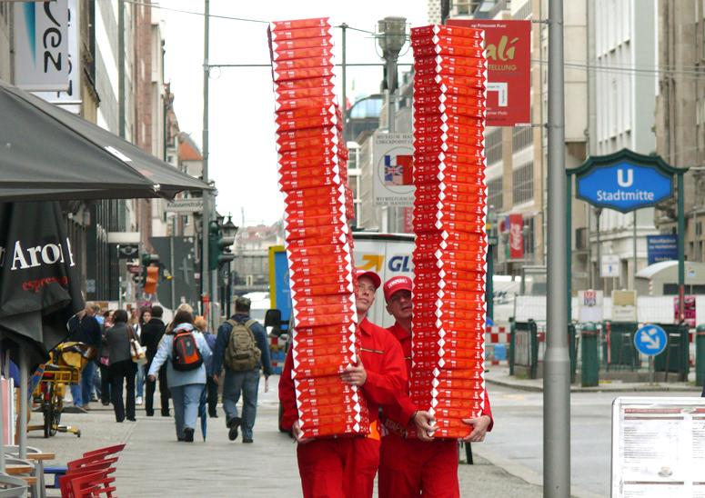 Mann trägt hohen Stapel Papier